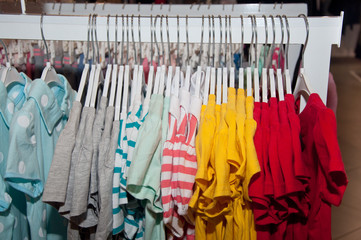 Bright t-shirts hanging in boutique