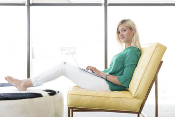 Caucasian woman sitting in chair using laptop