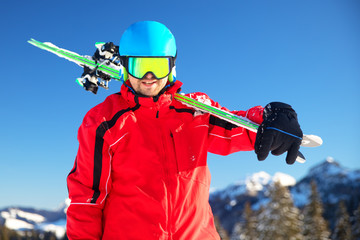 Young attractive caucasian skier with ski in Swiss Alps ready for skiing.