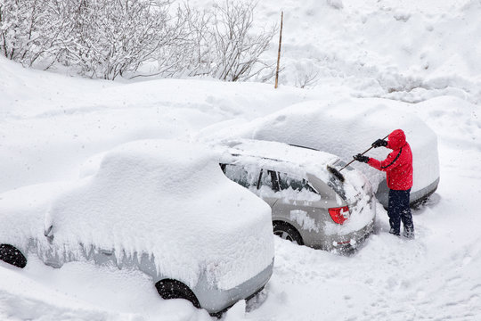 Young attractive man brushing the snow off his car on a cold winter day