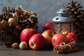 Red apples, cones and a flashlight with a candle