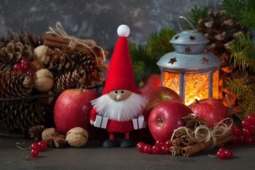 Christmas card with Santa toy. Red apples, berries, cones, nuts and a flashlight with a candle.
