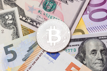 Bitcoin on background with dollar and euro money.