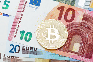 Golden Bitcoin close-up. Background euro currency. Conceptual photo.