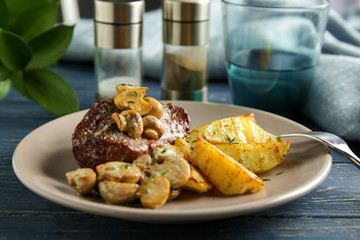 Plate with steak Diane and vegetable garnish on wooden table