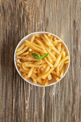 Bowl with yummy french fries on wooden table