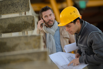 businessmen and architect in hard hats planning construction project