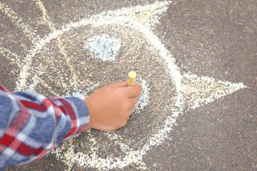 Little child drawing cat with chalk on asphalt, closeup