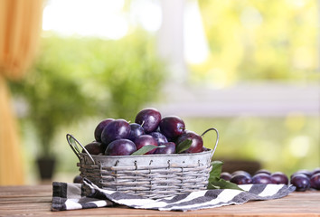 Fresh plums in wicker basket on table
