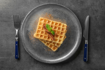 Metal plate with delicious cinnamon waffles on table
