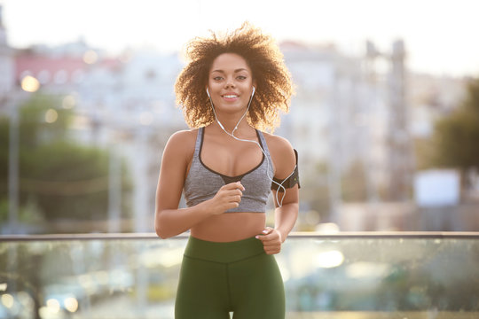 Sporty African American woman running outdoors