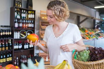 happy young woman customer choosing mango