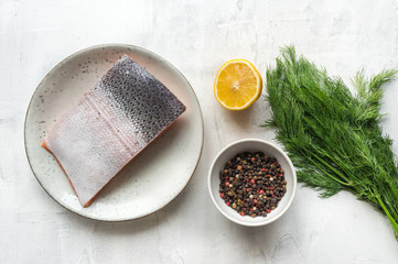Fresh salmon steak, lemon, pepper and dill on concrete table. Top view. Scandinavian ingredients for cooking from above.