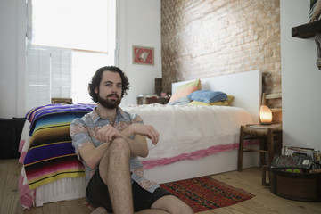 Portrait of young man sitting besides bed at home