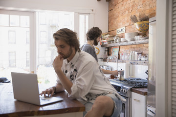 Young man using a laptop in his kitchen
