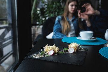 Tiger shrimps in Chinese noodles with sauce on black plate. Asian food concept. People on background in Restaurant place with wooden table. Flare copy space for text, design.