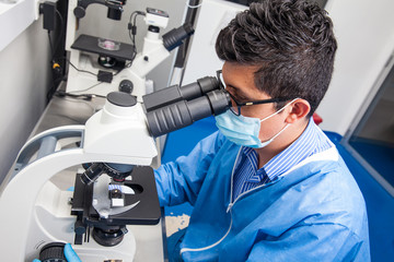 Young male scientist looking at slides under the microscope