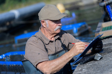 man writing notes in his clipboard while working in fish-farm