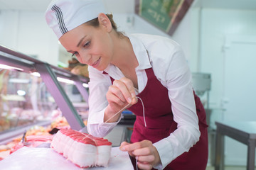 positive female butcher preparing product