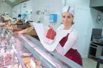 smiling female butcher with meat at the counter