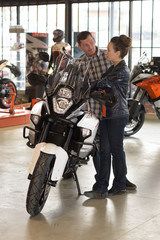 female seller and male client near motorcycle in store
