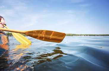 People paddling a canoe on a lake, shallow focus on  waves