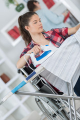 woman on wheelchair during ironing at home