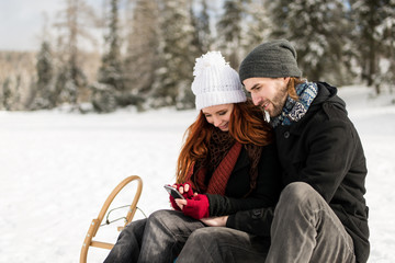 Couple in love using mobile while sitting on sleigh