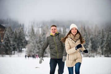 Playful teen couple playing in the snow