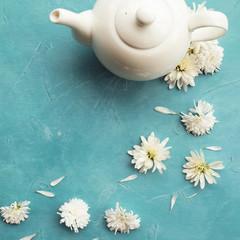 Hot healthy organic herbal tea. White teapot on blue background