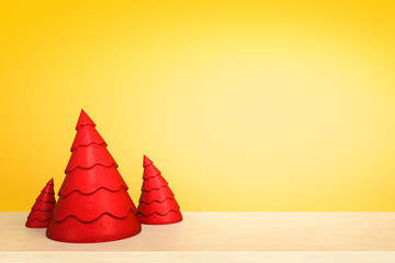 Christmas tree on wooden table in front of yellow background. Christmas holiday celebration concept, 3D rendering