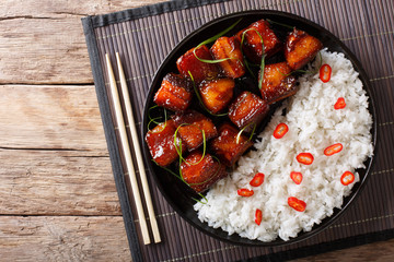 Vietnamese spicy caramel pork belly with rice closeup on a table. Horizontal top view