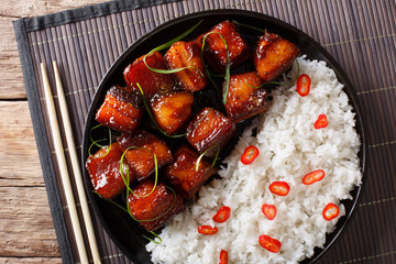 Glazed pork belly with rice close-up on a plate. Horizontal top view