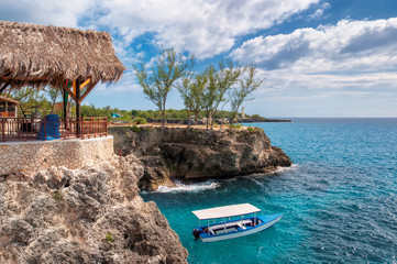 Caribbean rocky beach with turquoise water, tourists boat and lighthouse in Negril, Jamaica.