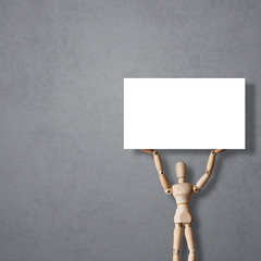 Wooden Mannequin on gray background holds up empty billboard or blank banner. Concept for advertisement or revolution protest