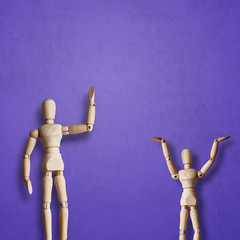 Two Wooden Mannequin wave hand with greeting on purple background
