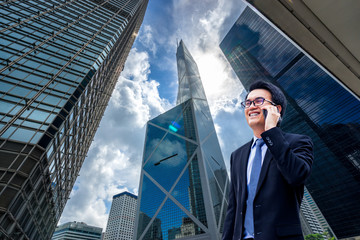 Portrait of asian handsome business man using cell phone, smiling, Hong Kong downtown business district background.