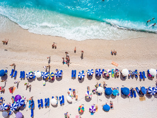 Aerial view of Egremni Beach Lefkada with tourists relaxing on the beach, swimming and playing games on a hot summer day