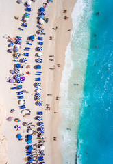 Tourists relaxing on the Egremni Beach in Lefkada swimming and playing games in the water