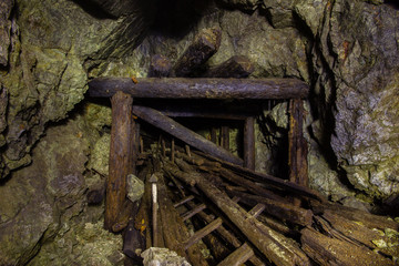 Underground mine shaft copper ore tunnel gallery with wooden stands timbering