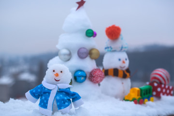 Snowman in blue coat on winter background