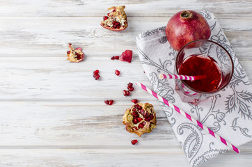 Pomegranate juice in glass and pomegranates  on white wooden background