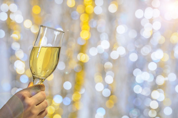 A glass of champagne in his hand on a bright blurred background.