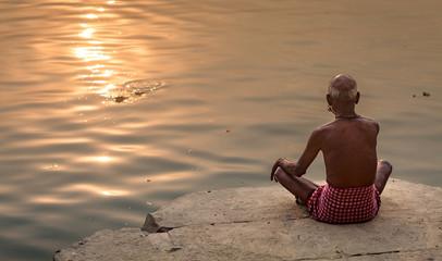 Old man meditates at the Ganges river ghat Varanasi, India at sunrise Wall mural