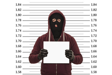 Police lineup or mugshot concept with a burglar or thief wearing a ski mask or balaclava and holding a blank white cardboard with copy space against a metric size chart with clipping path