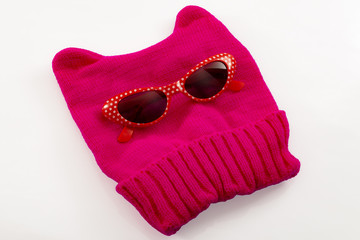 Advocacy of women's rights on the ground of the equality of the sexes and feminism concept,with a pink pussy hat and retro girly sunglasses isolated on white with clipping path