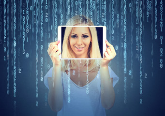Happy young woman holding tablet with her face displayed on a screen isolated on binary code background