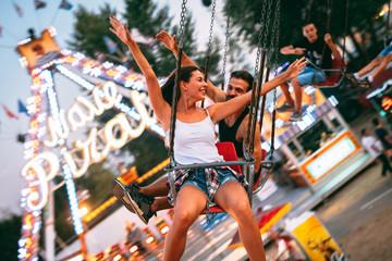 In de dag Amusementspark Young couple enjoying on the swings