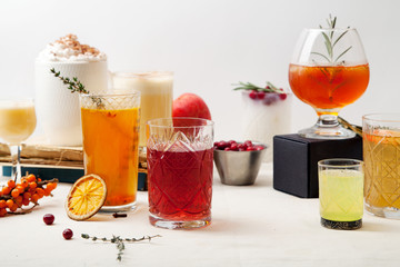 Set of various winter cocktails: mulled wine, eggnog, limoncello, old-fashioned, coconut margarita. White linen background.