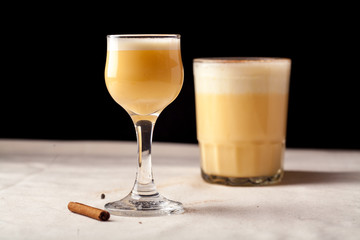 Two glasses with christmas eggnog drink decorated with cinnamon on dark background. Horizontal composition with copy space.